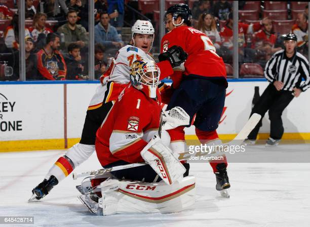 Micheal Ferland of the Calgary Flames is checked by Alex Petrovic a Goaltender Roberto Luongo of the Florida Panthers defends the net at the BBT...