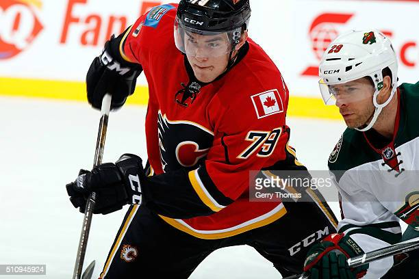 Micheal Ferland of the Calgary Flames skates against Jason Pominville of the Minnesota Wild during an NHL game at Scotiabank Saddledome on February...