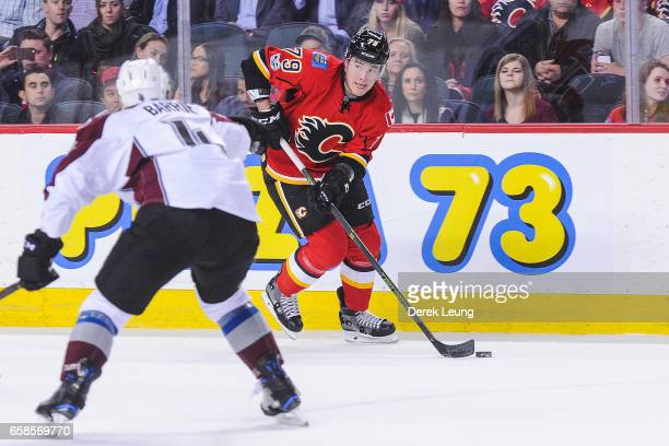 Micheal Ferland of the Calgary Flames skates with the puck against Tyson Barrie of the Colorado Avalanche during an NHL game at Scotiabank Saddledome...