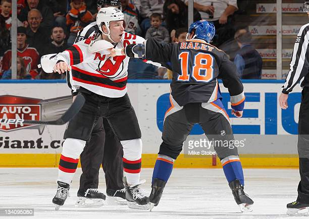 Micheal Haley of the New York Islanders gets tangled up with Cam Janssen of the New Jersey Devils at Nassau Veterans Memorial Coliseum on November 25...