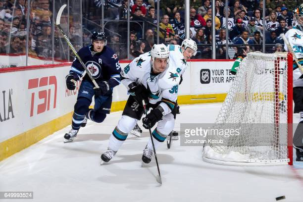 Micheal Haley of the San Jose Sharks and Mark Scheifele of the Winnipeg Jets chase the loose puck around the net during second period action at the...