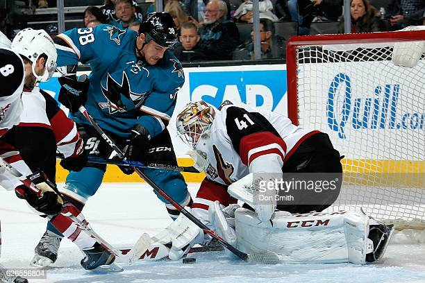 Micheal Haley of the San Jose Sharks tries to get the puck by Mike Smith of the Arizona Coyotes during a NHL game at SAP Center at San Jose on...