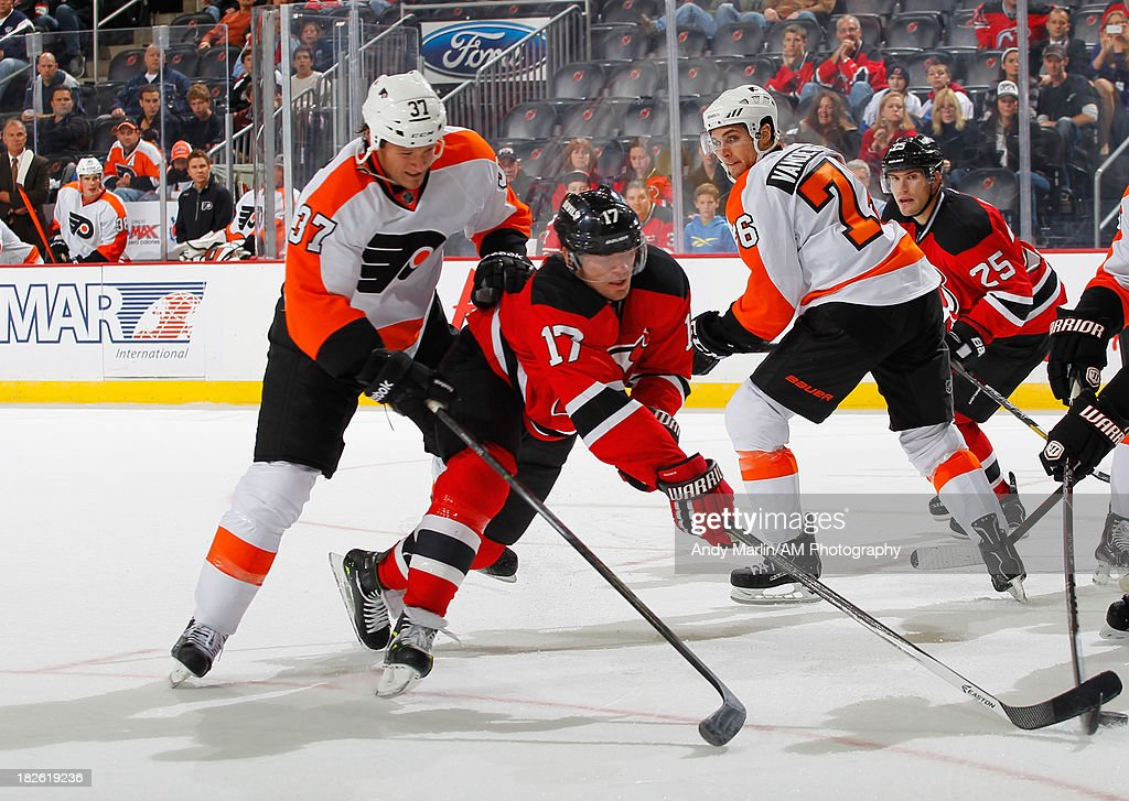 Micheal Ryder of the New Jersey Devils and Jay Rosehill of the Philadelphia Flyers battle for a loose puck during the preseason game at Prudential...