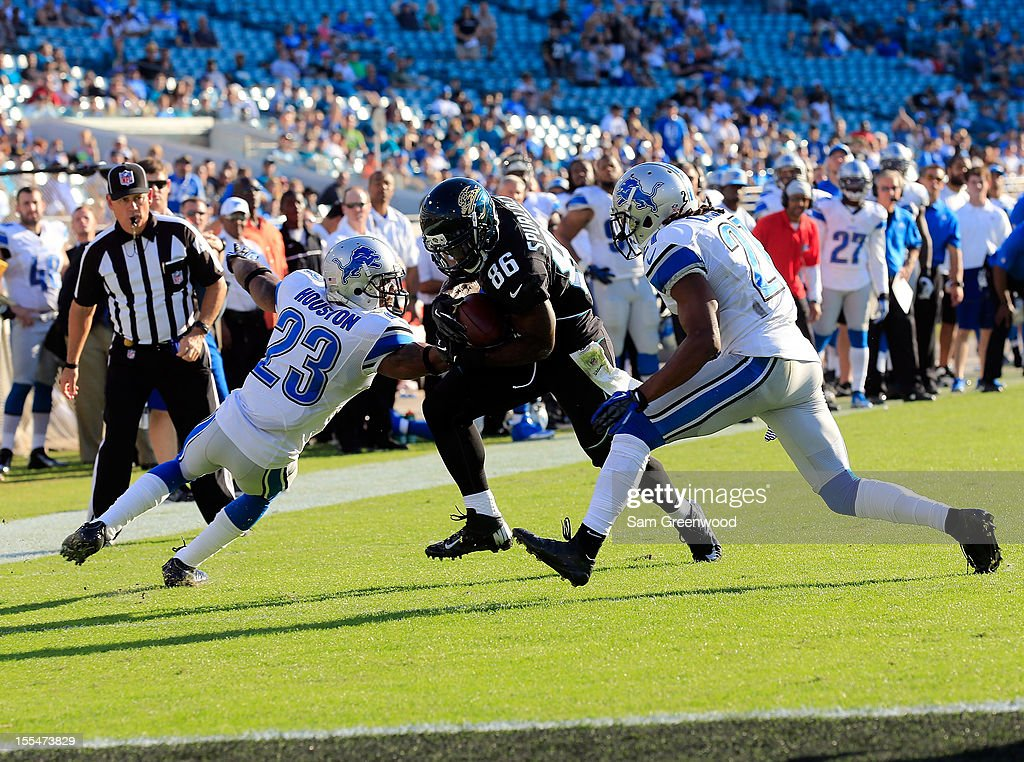 Micheal Spurlock #86 of the Jacksonville Jaguars runs past Chris Houston #23 of the Detroit Lions for a touchdown during the game at EverBank Field on November 4, 2012 in Jacksonville, Florida.