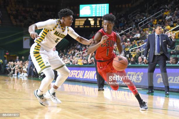 Micheal Warren of the Cal State Northridge Matadors dribbles the ball around Jaire Grayer of the George Mason Patriots during a college basketball...