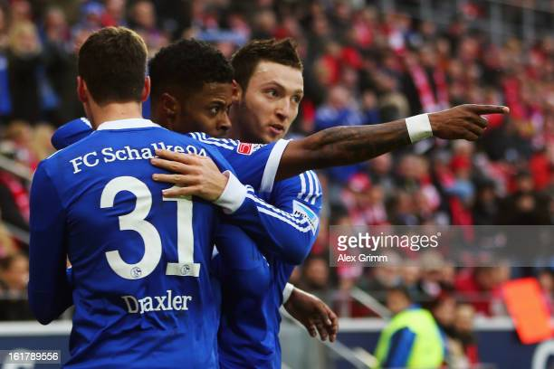 Michel Bastos of Schalke celebrates his team's first goal with team mates Julian Draxler and Marco Hoeger during the Bundesliga match between 1 FSV...