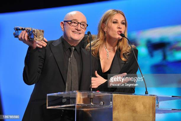 Michel Blanc smiles on stage with his Cesar for Best Supporting Actor as Mathilde Seigner speaks during the 37th Cesar Film Awards at Theatre du...