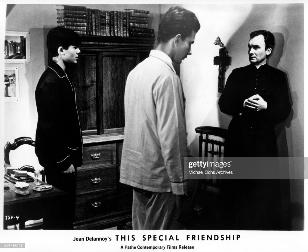 Michel Bouquet Francis Lacombrade stand in front of Francois Leccia at a Jesuit run school in a scene from the movie 'This Special Friendship' circa...