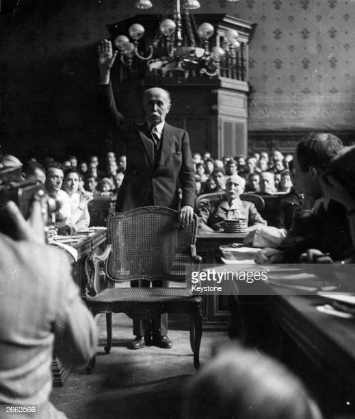 Michel Clemenceau son of Georges Clemenceau who presided over the Treaty of Versailles taking the oath at the trial of Henri Petain seated behind...