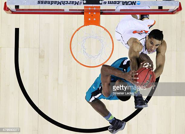 Michel Enanga of the Coastal Carolina Chanticleers and Malcolm Brogdon of the Virginia Cavaliers vie for a rebound during the Second Round of the...