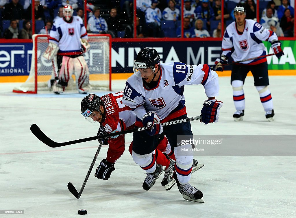 Michel Miklik (R) of Slovakia and Raphael Herburger (L) of Austria battle for the puck during the IIHF World Championship group H match between Slovakia and Austria at Hartwall Areena on May 10, 2013 in Helsinki, Finland.