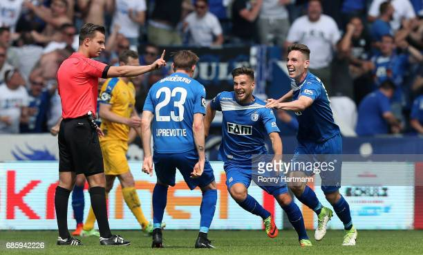 Michel Niemeyer of Magdeburg celebrates after scoring his team's opening goal with Florian Kath and Charles Elie Laprevotte of Magdeburg next to...