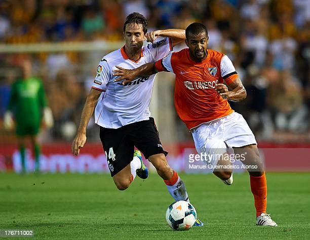 Michel of Valencia competes for the ball with Tissone of Malaga during the La Liga match between Valencia CF and Malaga CF at Estadio Mestalla on...