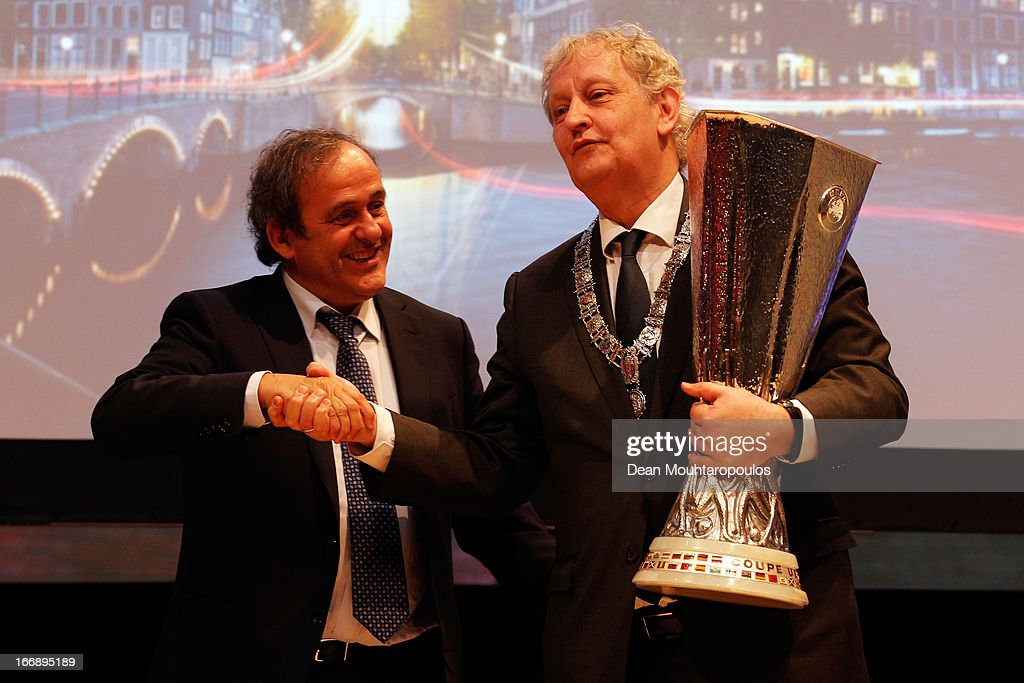 <a gi-track='captionPersonalityLinkClicked' href=/galleries/search?phrase=Michel+Platini&family=editorial&specificpeople=206862 ng-click='$event.stopPropagation()'>Michel Platini</a> (L), President of the Union of European Football Associations hands over the trophy to Eberhard E. van der Laan, Mayor of Amsterdam in front of the media and guests during the UEFA Europa League trophy handover ceremony at Beurs van Berlage on April 18, 2013 in Amsterdam, Netherlands. Amsterdam Arena will host the final of the UEFA Europa League on May 15.