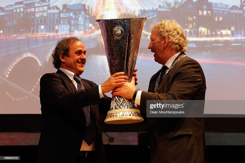 Michel Platini (L), President of the Union of European Football Associations hands over the trophy to Eberhard E. van der Laan, Mayor of Amsterdam in front of the media and guests during the UEFA Europa League trophy handover ceremony at Beurs van Berlage on April 18, 2013 in Amsterdam, Netherlands. Amsterdam Arena will host the final of the UEFA Europa League on May 15.