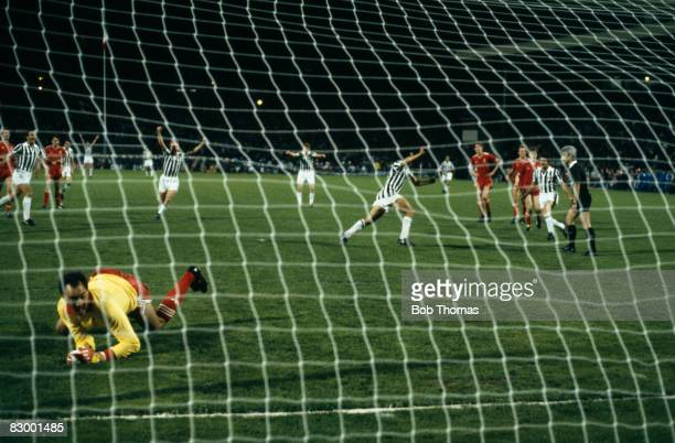 Michel Platini turns to celebrate after beating Liverpool goalkeeper Bruce Grobbelaar with a penalty kick to win the European Cup Final for Juventus...