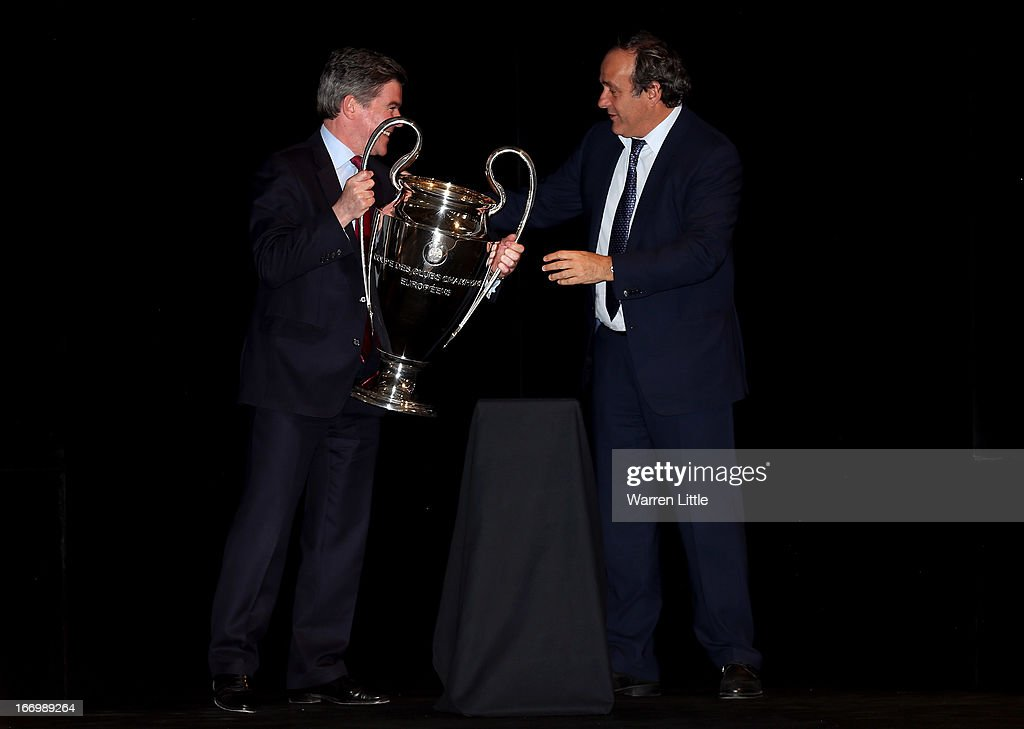 <a gi-track='captionPersonalityLinkClicked' href=/galleries/search?phrase=Michel+Platini&family=editorial&specificpeople=206862 ng-click='$event.stopPropagation()'>Michel Platini</a> , UEFA President hands the trophy to Hugh Robertson, UK Minister for Sport during the UEFA Champions League and UEFA Women's Champions League Cup handover ceremony at Banqueting House, Whitehall on April 19, 2013 in London, England. Wembley Stadium in London will host on May 25 the final football match of the UEFA Champions League.