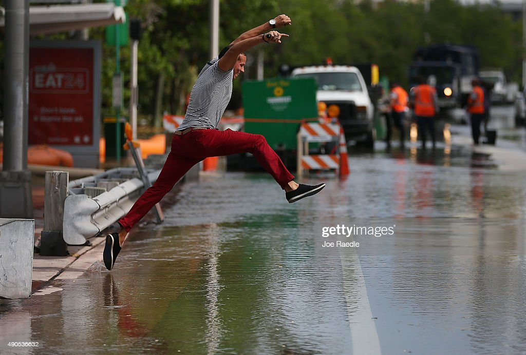Michel Rodriguez tries to jump to a shallow spot as he crosses a flooded street that was caused by the combination of the lunar orbit which caused...