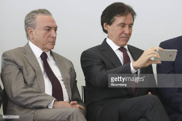 Michel Temer Brazil's president left listens as Eunicio Oliveira president of Brazil's senate uses a smartphone to take a photograph during the...