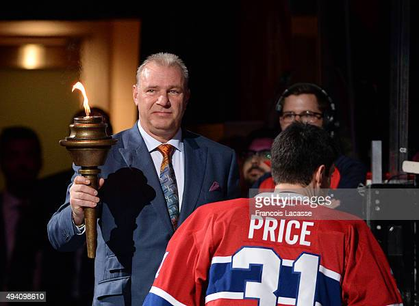Michel Therrien of the Montreal Canadiens holds the flame during the pre game ceremony prior to the NHL game against the New York Rangers at the Bell...