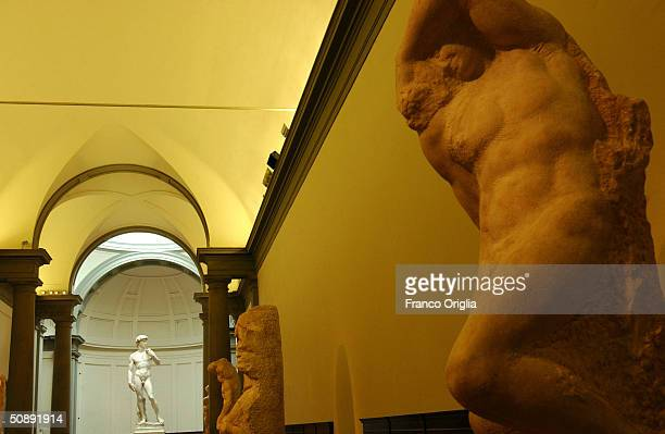 Michelangelo's scultures 'I Prigioni' and in the background restoration work on Michelangelo's masterpiece David is completed May 24 2004 at the...