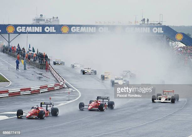 Michele Alboreto of Italy drives the Scuderia Ferrari Ferrari F1/87/88C Ferrari V6 ahead of team mate Gerhard Berger and the field in the rain at the...