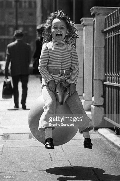 Michele Durlow bouncing on a Spacehopper models an outfit from Littlewoods' range of winter clothes for children