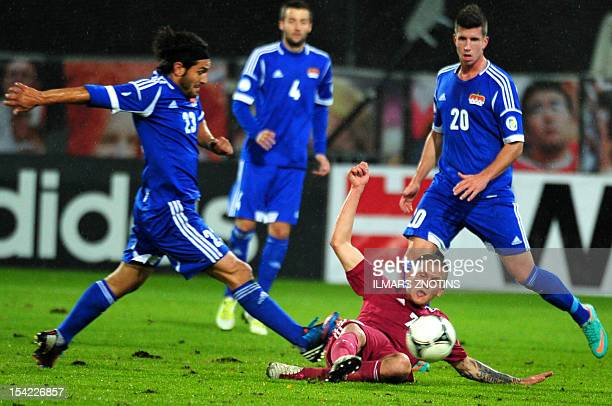 Michele Polverino and Sandro Wieser of Lichtenstein vies with Vladimirs Kamess of Latvia during the FIFA 2014 World Cup qualifying football match...
