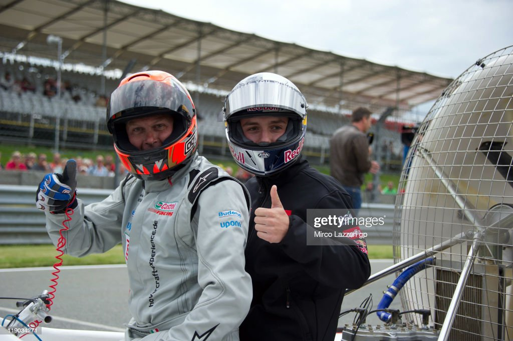Michele Scanavino of Italy poses with Jonas Folger of Germany and Red Bull Ajo Motorsport on the hovercraft during the preevent 'Riders from the 3...