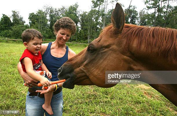 Michelle Akers and son Cody feed carrots to one of her horses at her Chuluota Florida home September 18 2007 Last time most Americans saw Michelle...