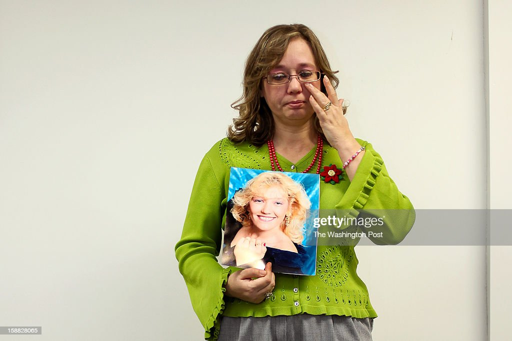 Michelle Davis wipes away tears as she holds a photograph of her sister, Gail Phok, who died in 2011 of drug-related health issues, on Thursday, December 20, 2012 in Portsmouth, Ohio. Davis volunteers at SOLACE, an organization that raises community awareness to the effects of prescription drug abuse.