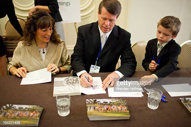 Michelle Duggar and Jim Bob Duggar stars of The Learning Channel TV show '19 Kids and Counting' pose for a picture with a fan while signing copies of...