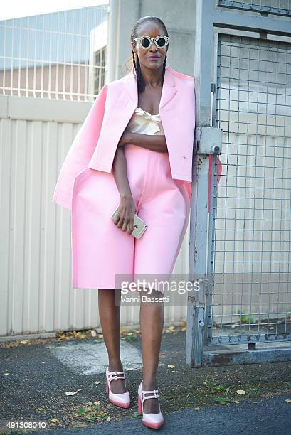 Michelle Elie poses wearing Comme des Garcons jacket and pants Miu Miu top and Prada shoes after the Kenzo show at the Paris Event Center during...
