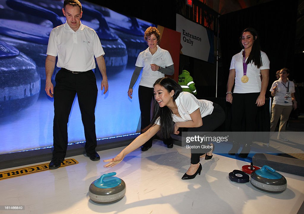 Michelle Kwan, figure skating, 1998 and 2002; and Aly Raisman, gymnastics 2012; briefly step away from posing for pictures with Liberty Mutual Insurance employees to try their hand at curling. Standing in background, left, are John Benton and Tracy Sachtjen, curling 2010. A new US Olympic Committee sponsor, the insurance company celebrates 'One Year Out' to the 2014 Olympic Winter Games in Sochi, Russia, on Thursday, Feb. 7, 2013.