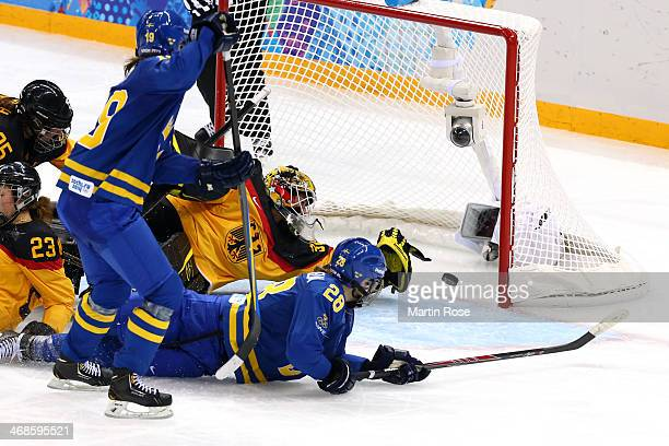 Michelle Lowenhielm of Sweden scores their third goal against Jennifer Harss of Germany in the third period during the Women's Ice Hockey Preliminary...