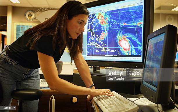 Michelle Mainelli a meteorologist looks at a computer monitor tracking hurricane Isabel at the National Hurricane Center September 12 2003 in Miami...