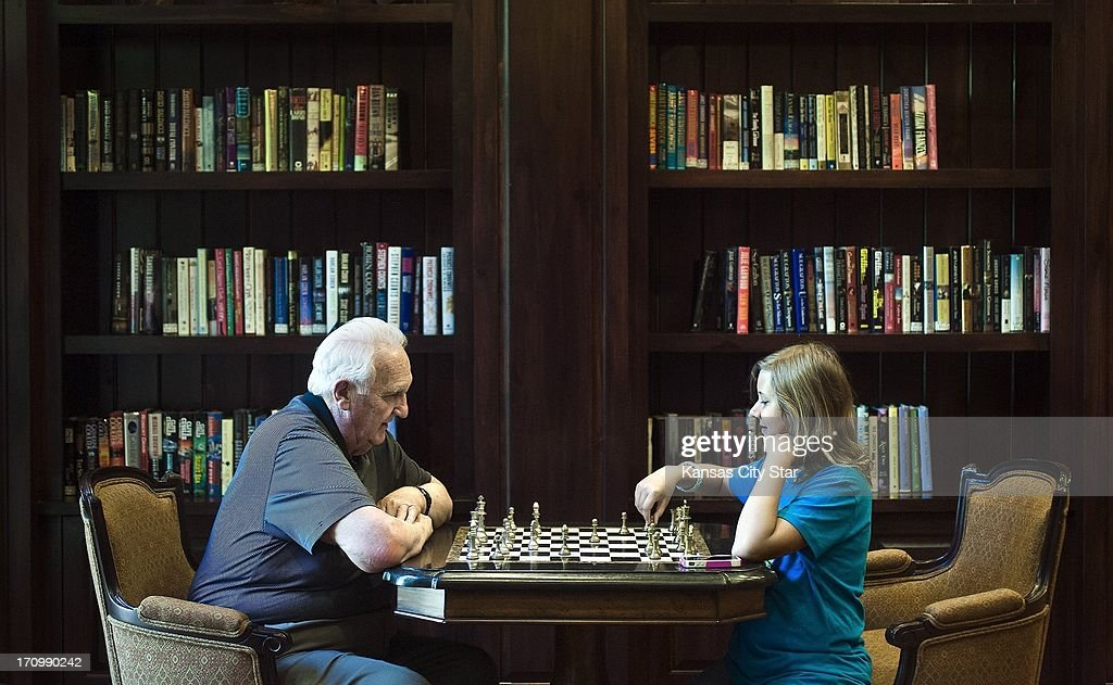 Michelle Meyer, 10, plays chess with her grandfather, Ed Hall, at the Santa Marta Senior Living Center on June 3, 2013, in Olathe, Kansas. Michelle spends two to three days a week with her grandfather.
