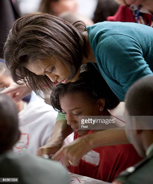 Michelle Obama helps a girl at Calvin Coolidge High School where students military families and volunteer service groups are working on various...