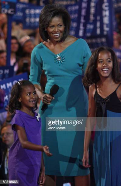 Michelle Obama wife of presumptive Democratic nominee US Sen Barack Obama stands with her daughters Sasha and Malia during day one of the Democratic...