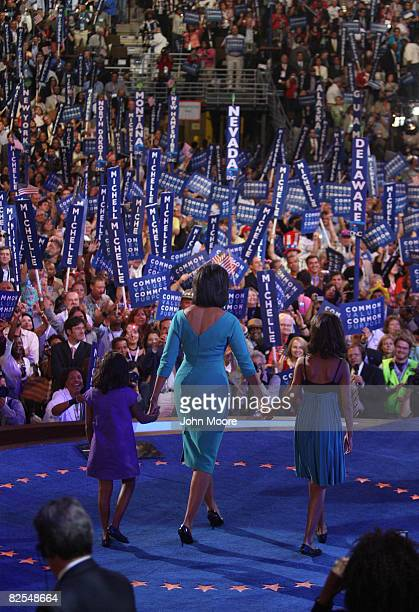 Michelle Obama wife of presumptive Democratic nominee US Sen Barack Obama walks on stage with her daughters Sasha and Malia during day one of the...