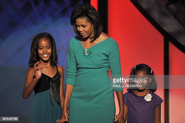 Michelle Obama wife of US Democratic presidential candidate Barack Obama brings daughters Malia and Sasha on stage after her speech at the Democratic...