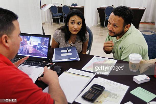 Michelle Ruiz and Nilson Ruiz listen as Wells Fargo home mortgage consultant Michael Carreras helps the potential homeowners with their an...