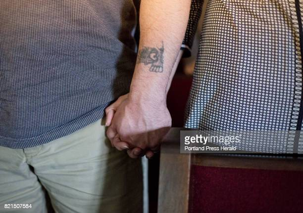 Michelle Sanborn holds hands with her husband Tony Sanborn as they attend a worship service at Apostolic Christian Life Center in Thomaston on Sunday...