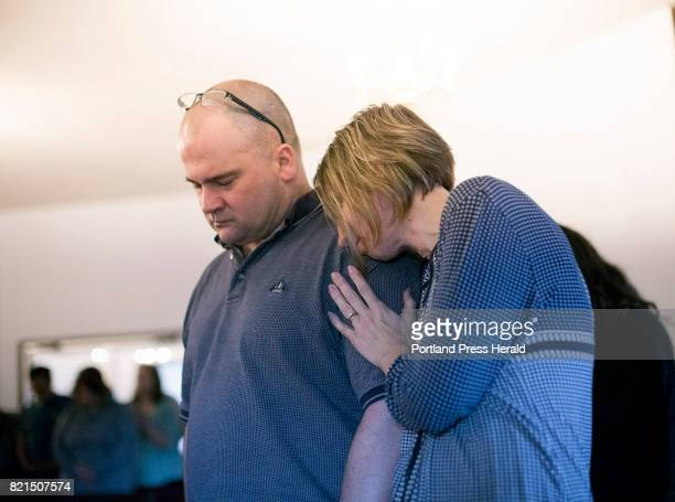 Michelle Sanborn rests her head on her husband Tony Sanborn as they attend a worship service at Apostolic Christian Life Center in Thomaston on...