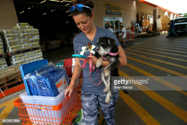 Michelle Smith checks her smart phone for news while clutching her dog Sophia as she leaves a Home Depot store with storm preparation supplies as...