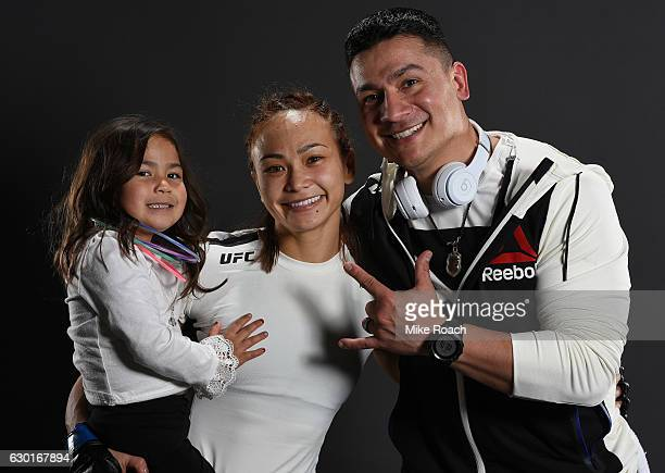 Michelle Waterson her daughter Araya and her husband Joshua Gomez pose for a portrait backstage after her victory over Paige VanZant during the UFC...