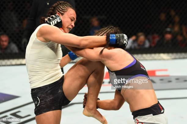 Michelle Waterson lands a knee to the chin of Tecia Torres in their women's strawweight bout during the UFC 218 event inside Little Caesars Arena on...