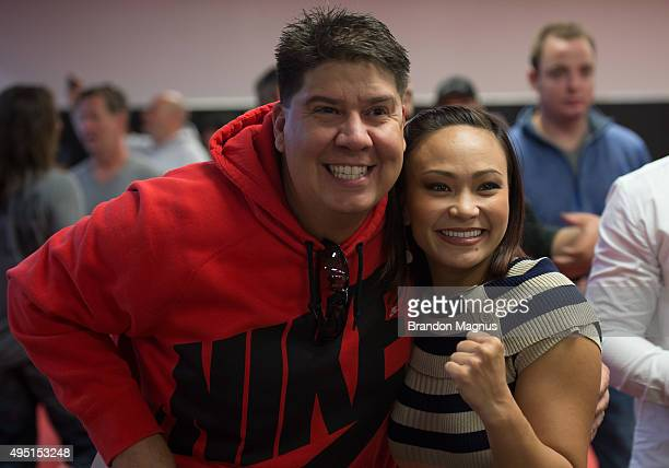 Michelle Waterson takes a picture with a fan during the Jackson Wink MMA Academy Grand Opening at Jackson's Mixed Martial Arts Fitness on October 31...