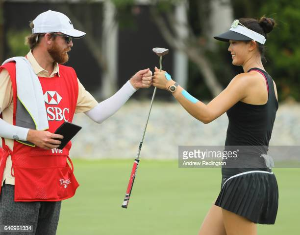 Michelle Wie of the United States celebrates with her caddie after a birdie on the 17th hole during the first round of the HSBC Women's Champions on...