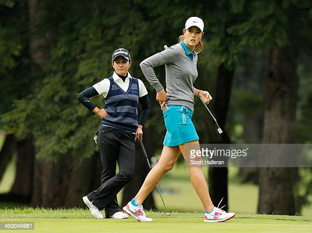 Michelle Wie of the USA and Ai Miyazato of Japan wait on the second green during the third round of the Lorena Ochoa Invitational Presented by...